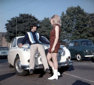 Posing on the bonnet of his car with his Miss UK girlfriend Jennifer Lowe in 1966