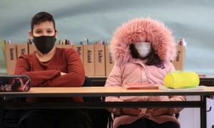 A schoolgirl wears a winter coat in the classroom in Bonn, Germany