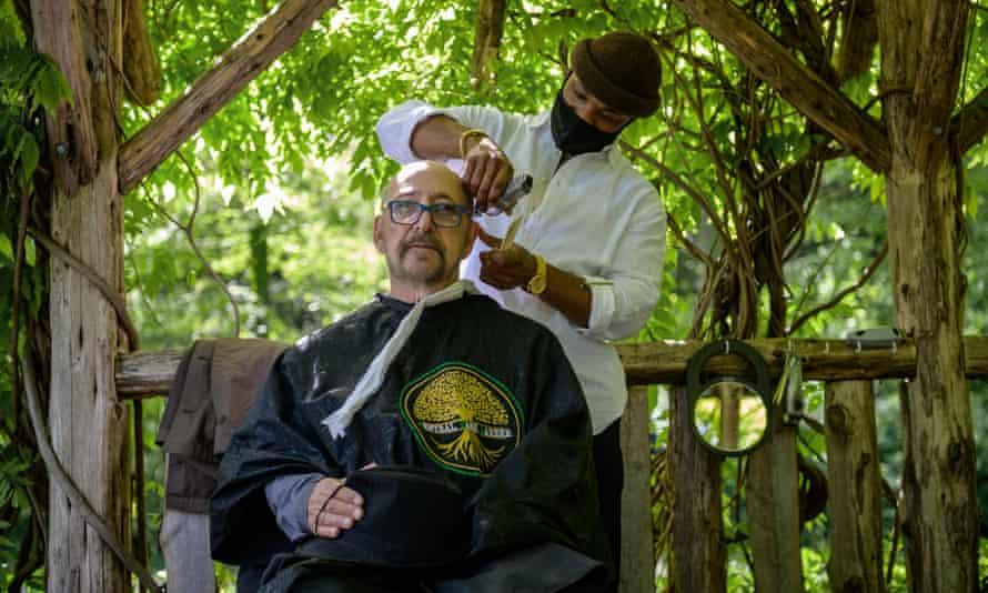 آرایشگر هرمان جیمز موهای مشتری را زیر آلاچیق در پارک مرکزی در شهر نیویورک کوتاه می کند.