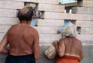 A man and a woman, naked from the waist up, peering through gaps in a brick wall. Taken from behind