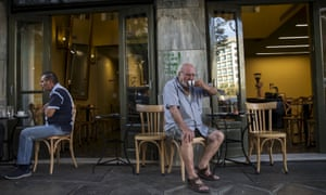 People sit outside of a coffee shop in Athens, Greece.