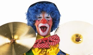 A clown holding a pair of cymbals