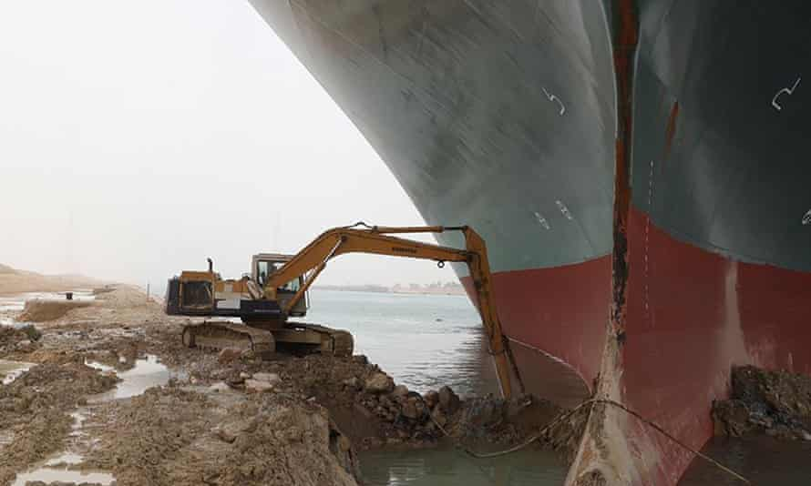 A work crew using excavating equipment tries to dig out the Ever Given wedged across the Suez Canal
