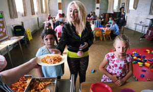Young familes are served hot food at St Teilo Church in Swansea, UK