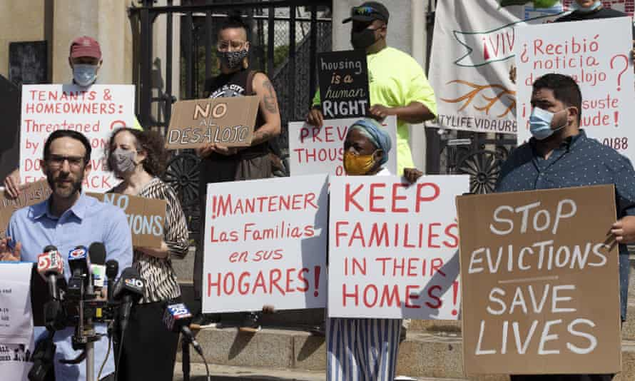 People from a coalition of housing justice groups hold signs protesting evictions in Boston.