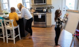 Farrah Eaton assists her daughters with home schooling on 18 March in New Rochelle, New York.