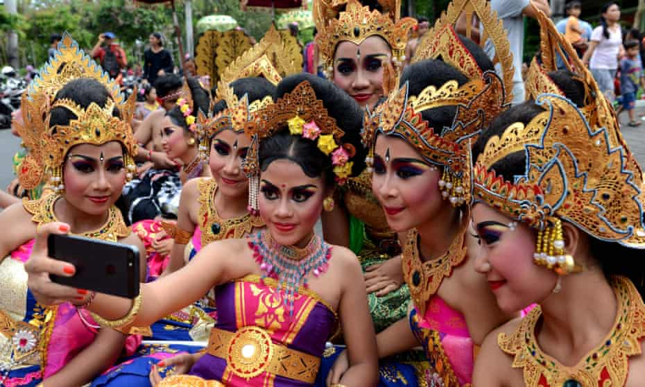 Balinese young girl take a selfie during a New Year celebration in Denpasar, on Indonesia's resort island of Bali.