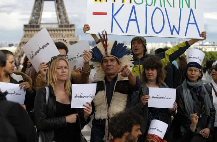 Ladio Veron (C), a leader of  indigenous Guarani Kaiowá tribe, stands in front of the Eiffel tower in Paris on 20 May during his tour to ask for help to fight against the agribusiness that threatens their population in the mato Grosso do Sul, Brazil