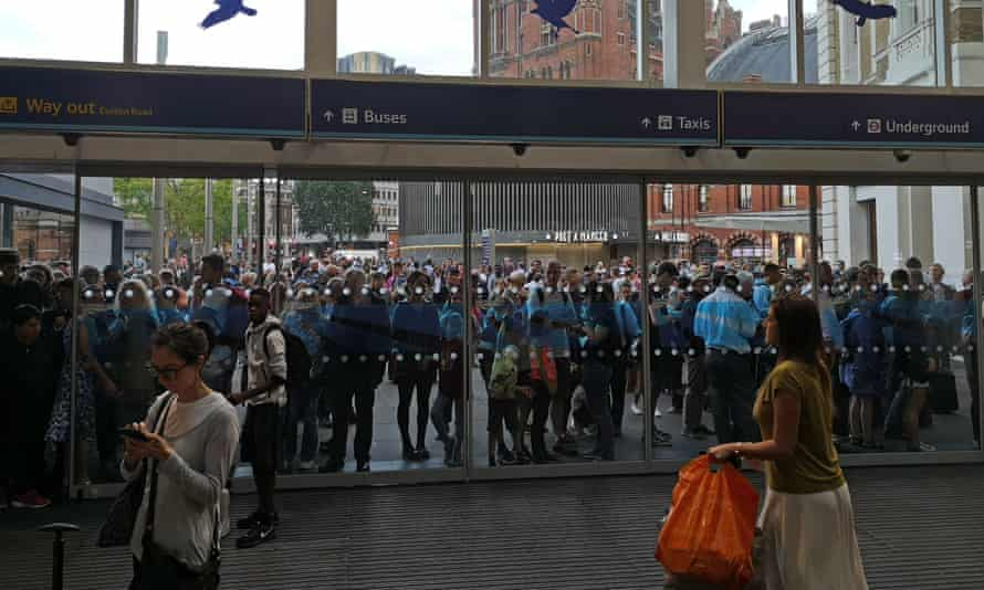 People waiting outside King's Cross station, London, as all services in and out of the station were suspended.