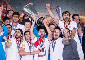 Sevilla celebrate as Coke lifts the trophy.