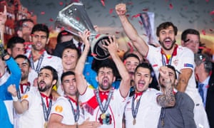 Sevilla captain and double goal-scorer Coke lifts the Europa League trophy high. The Spanish side made history after winning their third successive Europa League final.