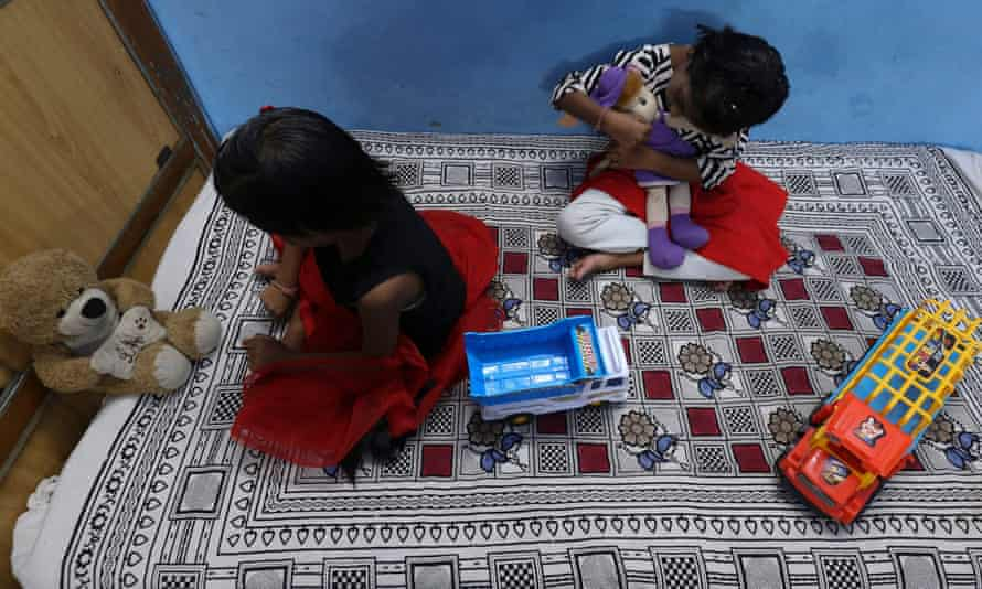 Twin sisters Tripti and Pari, who lost both their parents due to the Covid-19 coronavirus, play with their toys at a relative's home in Bhopal.