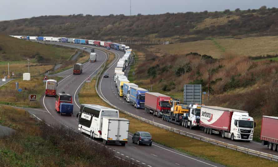 Lorries queue on the A20 to enter the port of Dover in Kent. A ban on travel to France has added another layer of complexity to Christmas stockpiling and Brexit uncertainty.