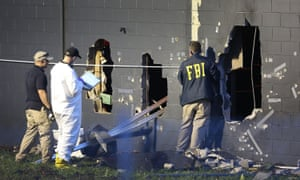 FBI agents investigate near the damaged rear wall of Pulse on Sunday in Orlando, Florida.