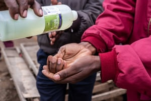 A matatu conductor gets his hands disinfected