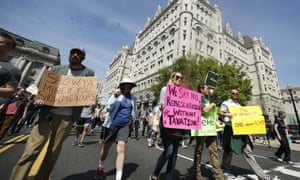 Protesters march past the Trump International Hotel in Washington, 15 April, 2017.