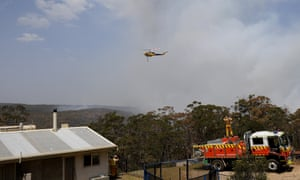 Firefighters watch a helicopter water bomb bushland
