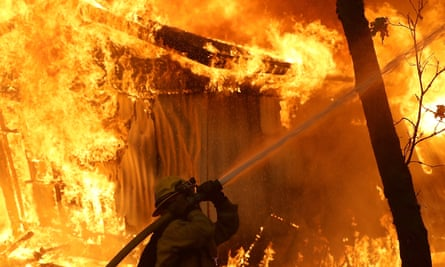 A Cal Fire firefighter monitors a burning home as the Camp fire moves through the area on 9 November 2018 in Magalia, California.