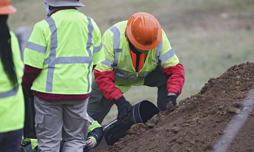 Researchers and work crews look at items pulled from the ground during the search for remains in Tulsa, Oklahoma, on 20 October.
