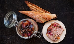 A slice of terrine of pork and smoked bacon next to a pot of cranberries and some toasted bread