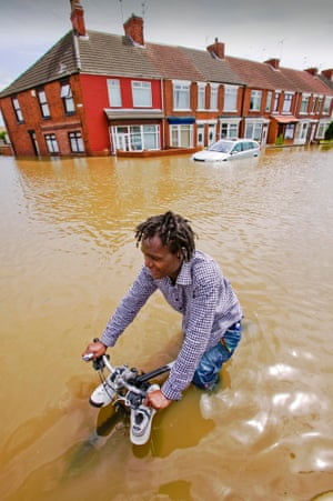 A young man cycles through flood waters in Toll Bar, South Yorkshire, UK
