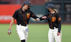 Alyssa Nakken greets San Francisco Giants outfielder Hunter Pence with an elbow tap during a game against the Oakland A's.