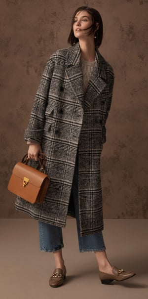 Model in long checked coat, jeans and brown leather handbag