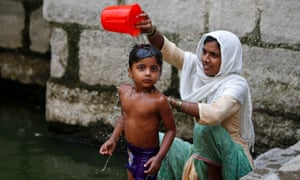 A woman bathes her child at a stepwell on a hot summer day in New Delhi.