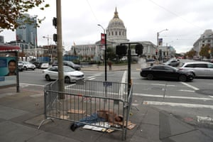 A homeless man sleeps on the sidewalk across from San Francisco's city hall.