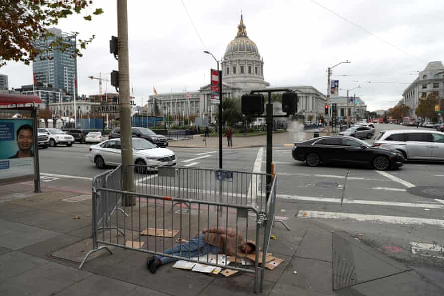 A homeless man sleeps on the sidewalk across from San Francisco's city hall.