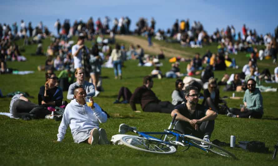 People enjoy the sunshine on Primrose Hill in London on Easter Sunday before the expected drop in temperature.