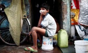 A boy wears a face mask in a slum area of Delhi, India