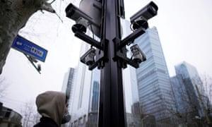 A man wearing a face mask walks under surveillance cameras