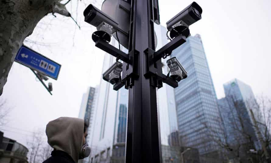 A man wearing a protective face mask walks under surveillance cameras in Shanghai