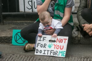 A child holds a sign pleading for action