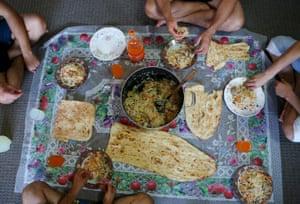 Four Hazara asylum seekers sit down to a meal of qabuli palaw with fresh Afghan bread