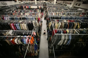 A warehouse worker walks between racks of costumes