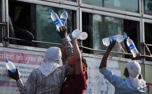 Hawkers offer bottles of water to passengers on a bus in Allahabad