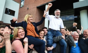 Sinn Fein's  Gerry Adams and fellow County Louth candidate Imelda Munster are lifted in celebration after Adams was re-elected