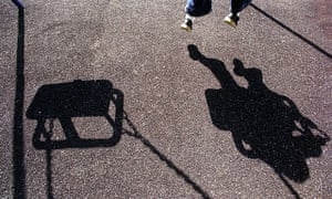 The shadow of a young child playing on a swing