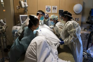 Medical personnel treat a coronavirus patient at Providence Holy Cross medical center in the Mission Hills section of Los Angeles last month.