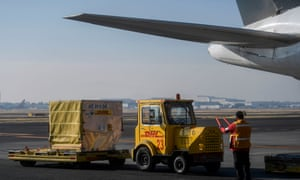 Workers unload containers carrying Mexico's second shipment of the Pfizer/BioNTech Covid-19 vaccine from a plane at Benito Juarez international airport in Mexico City