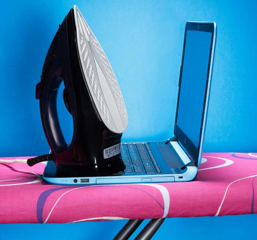Iron and laptop on ironing board, against blue and pink background