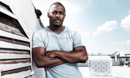 Idris Elba in a pale blue t-shirt on a rooftop
