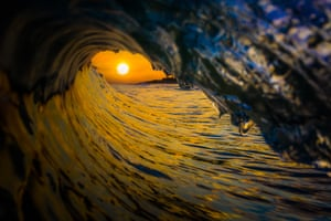 The sun framed by the barrel of the wave in Long Island, summer 2019