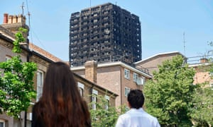 The burned-out shell of the Grenfell Tower block is seen behind terraced houses as local residents look on near the scene of the fire in North Kensington, west London.