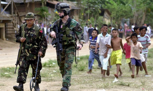 A US special forces member walks with a Filipino soldier in the southern Philippines in 2002.