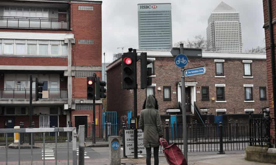 A woman photographed from behind pulling a shopping trolley at a pedestrian crossing, with two large skyscrapers behind the low-rise urban street