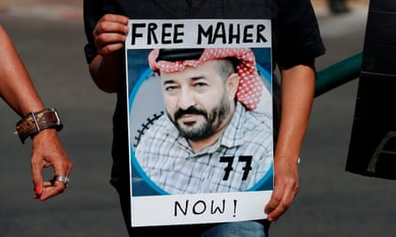 An Israeli activist holds a picture of hunger striker Maher al-Akhras