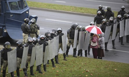 Two people face a line of riot police during a protest in Minsk
